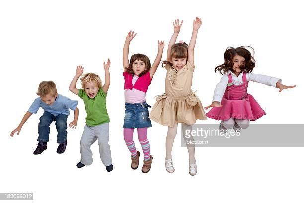 Group of happy young children jumping indoors
