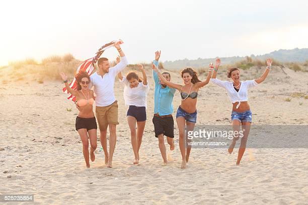 Eine Gruppe von glücklich junge Menschen Spaß haben zusammen am Strand