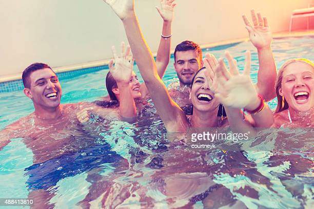 Group of happy young people partying in a pool.