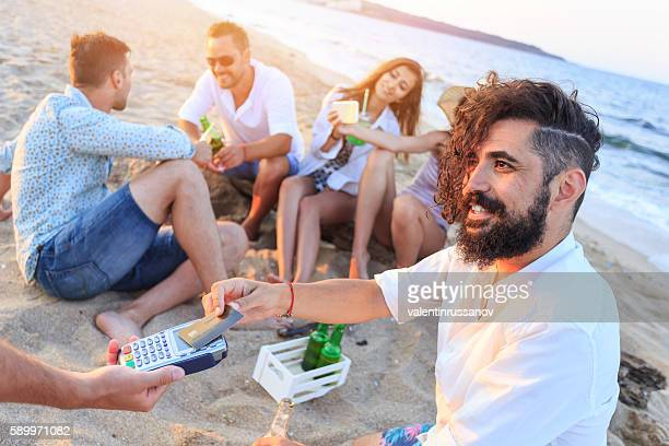 Group of happy young people using credit card on beach