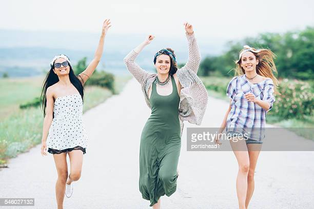 Group of happy young women dancing on the road