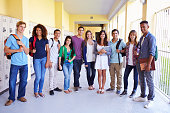 Group Of High School Students Standing In Corridor Smiling To Camera
