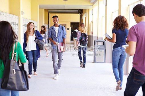 Group Of High School Students Walking Along Hallway : Stock Photo