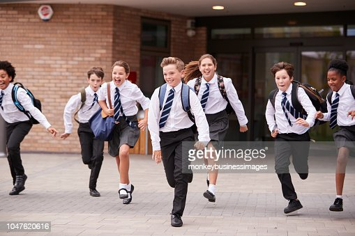 Group Of High School Students Wearing Uniform Running Out Of School Buildings Towards Camera At The End Of Class : Stock Photo