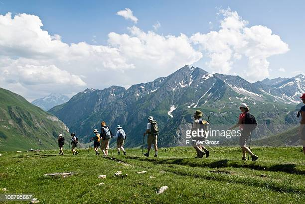 A group of hikers trek across a green mountainside on a partly cloudy day above Chamonix, France.