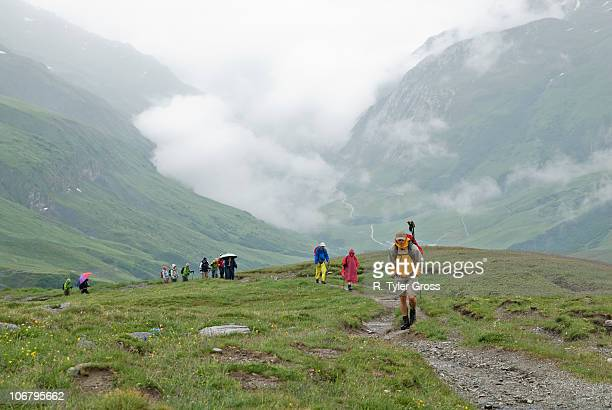 A group of hikers trek ot of a valley in the Alps during a rainstorm.