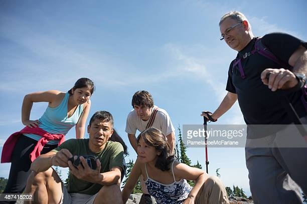 Group of Hikers Using GPS Mapping Application on Mobile Phone