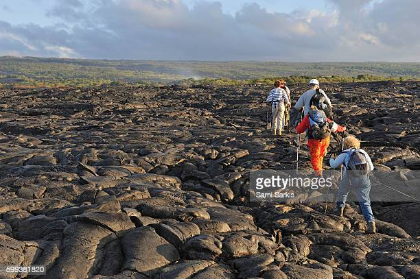 Group of hikers walking on cooled pahoehoe lava flow at sunrise, Kilauea Volcano, Big Island, Hawaii Islands, USA