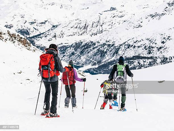 Group of hikers with snowshoes in the snowy mountains