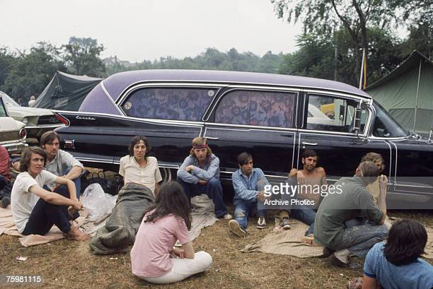 A group of hippies at an outdoor rock festival circa 1970 The car behind is a 1959 EurekaCadillac
