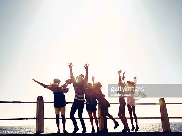 Group of hipster friends celebrating their vacations at the beach