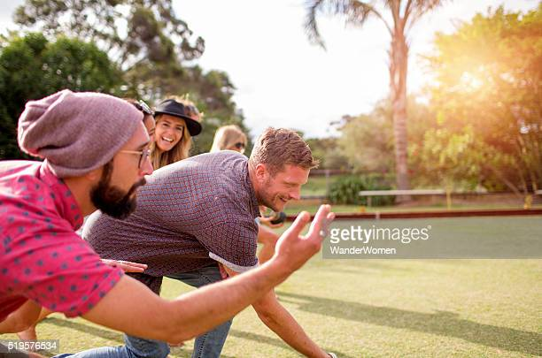 Group of hipster friends playing lawn bowls at sunset