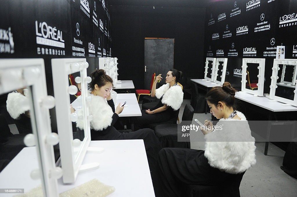 A group of hostesses look at their cellphones backstage after the Korean Designers' Collection at the China Fashion Week in Beijing on March 29, 2013. China Fashion Week runs from March 24 to March 30