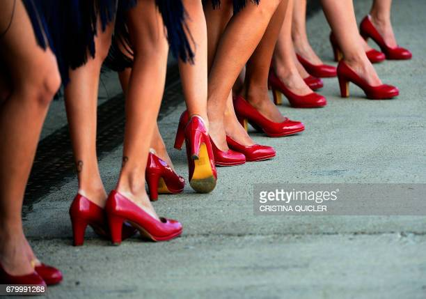 A group of hostesses popularly known as 'paragueras' wear red shoes as they pose on the pitlane before the Spanish Red Bull Grand Prix Moto 3 race at...
