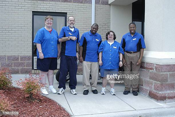 A group of housekeeping staff posing outside the building.
