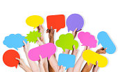 Group of human arms raised with multi coloured speech bubble.