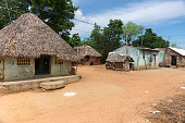 Kumbakonam, India - October 11, 2013: A group of humble houses, some with straw roofs stand at a dusty, sandy street against the background of green trees and a blue sky.
