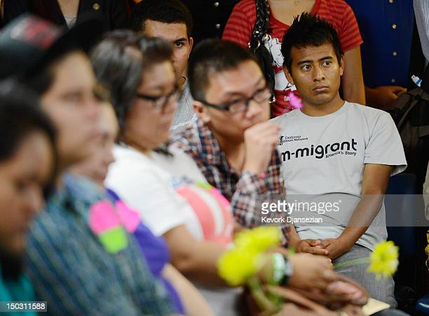 A group of immigrants known as DREAMers hold flowers as they listen to a news conference to kick off a new program called Deferred Action for...
