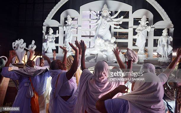 A group of Indian Hindu widows from the north Indian city of Vrindavan sing devotional songs as they visit a Pandal the makeshift worship place of...