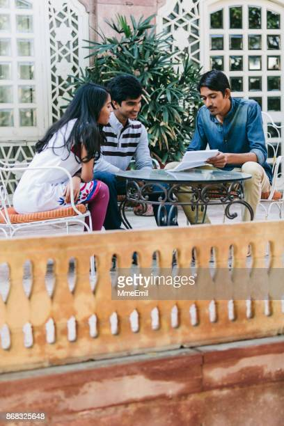 Group of indian millennials looking at a document around a table on a patio.