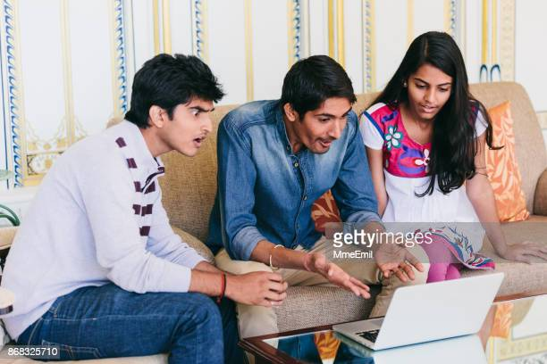 Group of indian millennials looking at a laptop and reacting at something together.