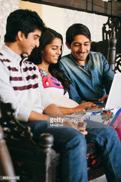 Group of indian millennials looking at a laptop and talking about business, homework or project together.