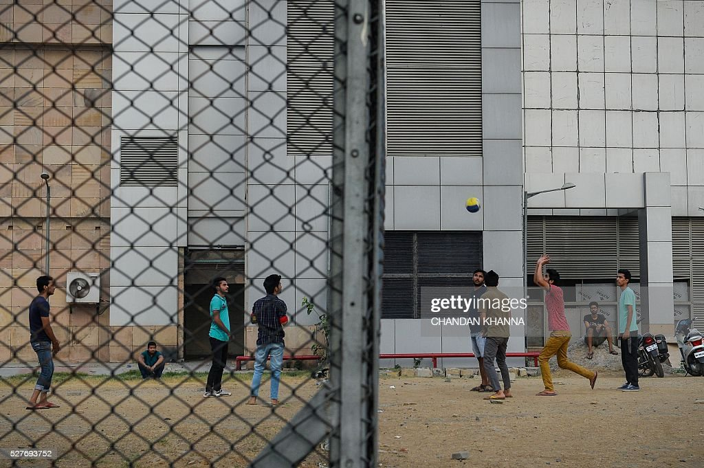 A group of Indian youths use fencing at a metro station to play volleyball in New Delhi on May 3, 2016. / AFP / CHANDAN