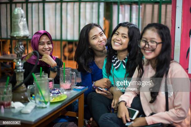A 'WARKOP' IN SURABAYA EAST JAVA SURABAYA INDONESIA A group of Indonesia girls are seen drinking tea and smoking shisha at a Warkop after school...