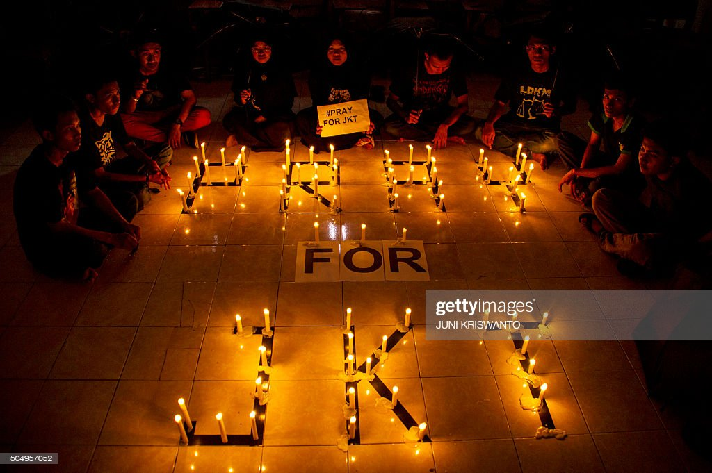 A group of Indonesian students hold placards during a candlelit protest in Surabaya Eastern Java island on January 14 to condemn the blasts and...