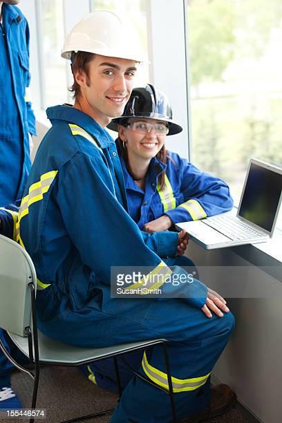 Gruppo di lavoratori industriali A un computer portatile