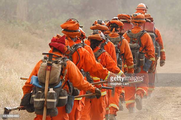 A group of inmate firefighters marches from their drop point on Morgan Valley Road to battle the Jerusalem Fire on August 11 2015 near Lower Lake...