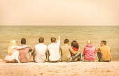 Group of international multiracial friends sitting at the beach talking with each other and contemplating the sea - Concept of multi cultural friendship against racism - Warm vintage filtered look