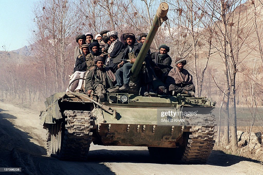 A group of Islamic militants members of the Afghan religious Taliban militia move toward the front line on a tank captured from HezbiIslami faction...