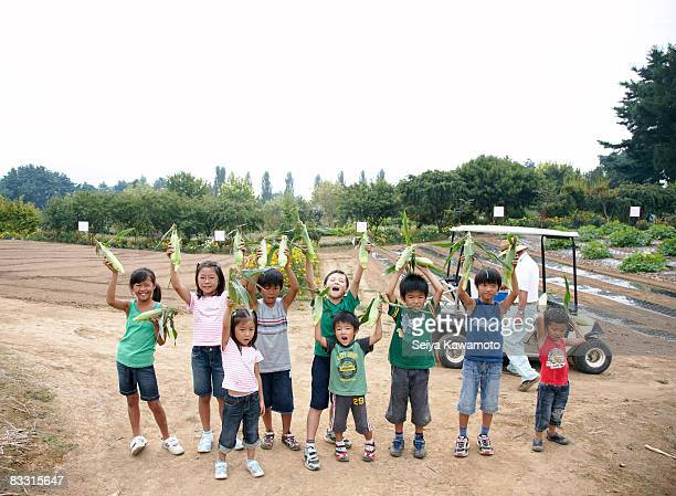A group of Japanese kids holding corn