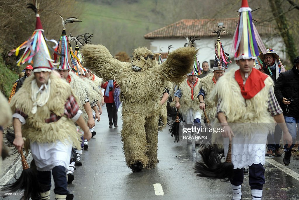 A group of 'Joaldunak' ('those who play the bell') and a man dressed as Hartza (bear) (C) march carrying big cowbells tied to their backs as they take part in the ancient carnival of Ituren, in the northern Spanish province of Navarra province, on January 28, 2014. The yearly three day festivities, revolving mainly around agriculture and principally sheep hearding, run on the last Sunday, Monday and Tuesday of January where Navarra Valley locals from three villages dress up and participate in a variety of activites as they perform a pilgrimage through in each village.