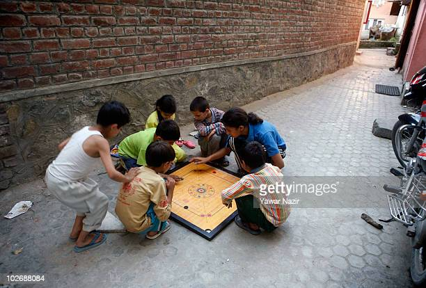A group of Kashmir children play carom board game in an alleyway during curfew on July 7 2010 in Srinagar the summer capital of Indian administered...