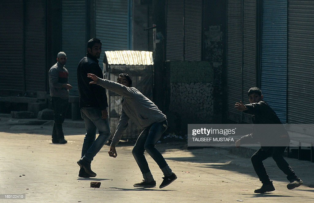A group of Kashmiri protestors throw stones towards Indian police during a spontaneous strike to protest the death of 28 year old Kashmiri student, Mudassir Qamran Malla in the Indian city of Hyderabad at the weekend, in Srinagar on March 5, 2013. The Kashmiri student was buried in his native village in the Pulwama district on Monday with the family rejecting the police claim that he had commited suicide. AFP PHOTO/Tauseef MUSTAFA