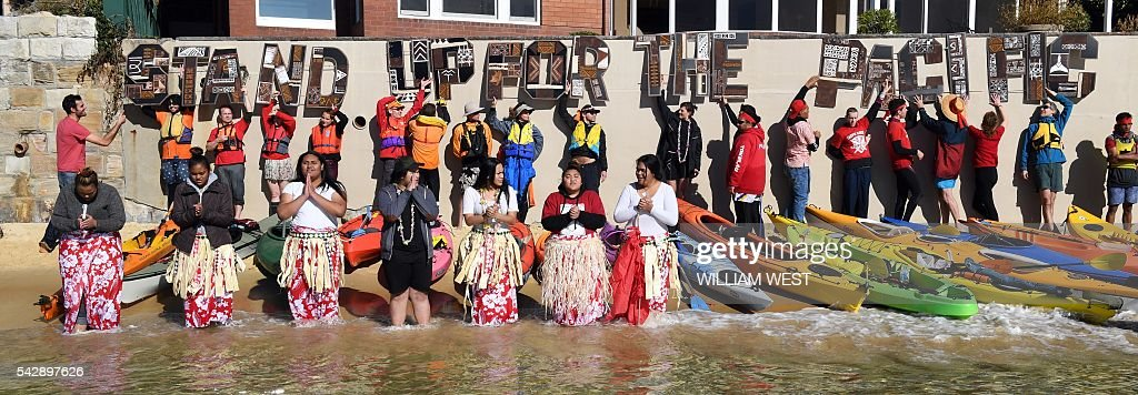 A group of kayakers, including members of Australia's Pacific islander community, hold up letters spelling out 'stand up for the Pacific' after they paddled to a tiny beach outside Australia's Prime Minister Malcolm Turnbull's Point Piper mansion (not in picture) in Sydney on June 25, 2016, protesting against what they say is government inaction on global warming. Among protesters were members of the Tokelau community, some dressed in woven skirts, who sang about the ocean around their homeland which is at risk of disappearing under the waves if climate change continues unabated. / AFP / WILLIAM