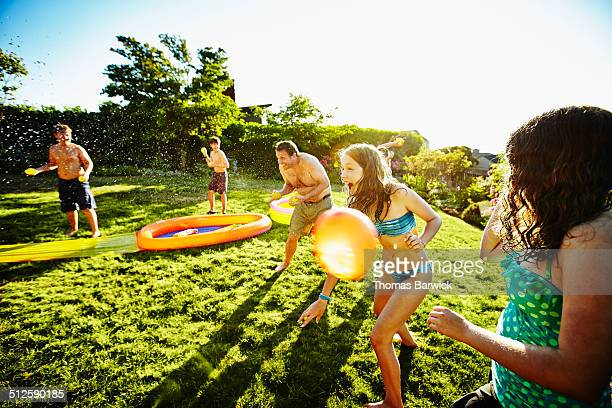 Group of kids and dad having water balloon fight