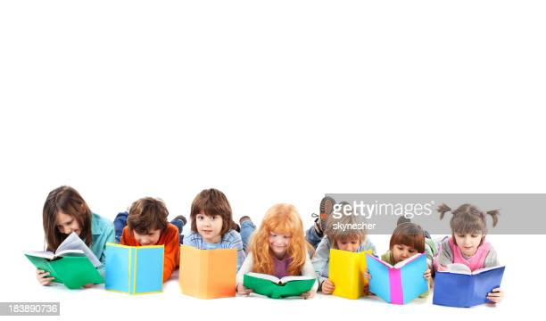 Group of kids are lying on floor and reading books.