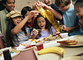 Group of kids (12-14)        around table, boy pouring mustard in food