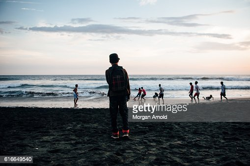 A group of kids from a rural village in Nicaragua play a game of football on the beach while the sun goes down : Stock Photo