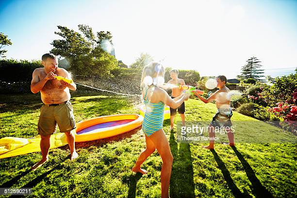 Group of kids having water fight with dad
