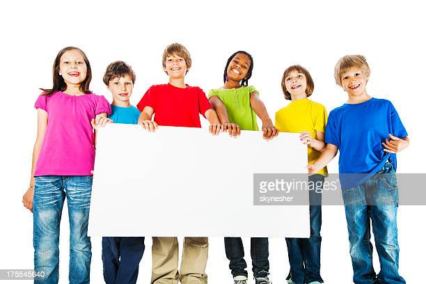 Group of kids holding a big white board.