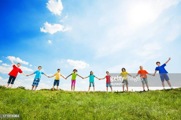 Group of kids holding hands against the sky.