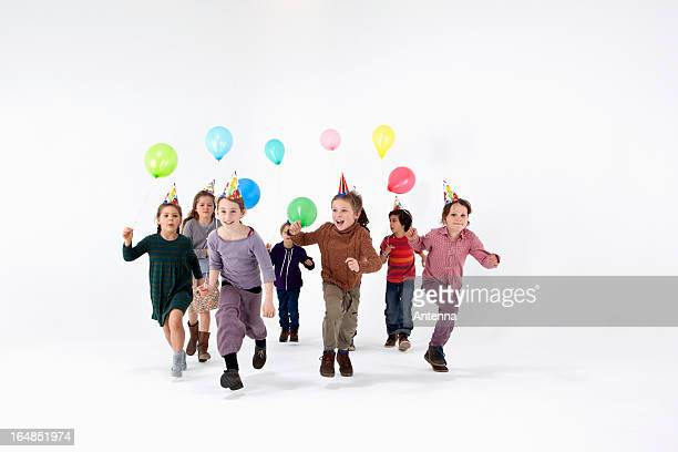 A group of kids in party hats and carrying balloons running forward