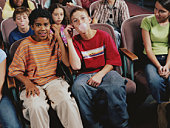 Group of kids (12-14) in room, boys with headphones blowing bubble