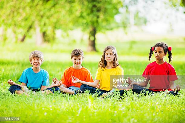 Group of kids meditating in a park.