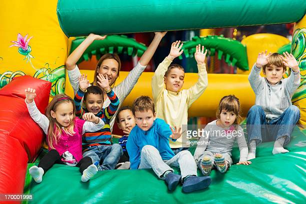 Group of kids on an indoors inflatable slide.