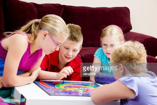 Group Of Kids Playing Board Game In A Living Room Stock Photo